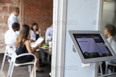 Screen Of Digital Tablet Booking System Outside Modern Boardroom