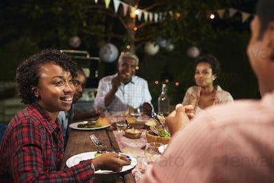 Adult black family eat dinner in garden, over shoulder view