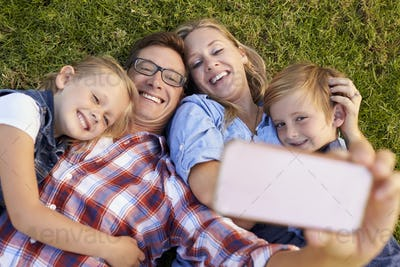 Young white family lying on grass in a park taking a selfie
