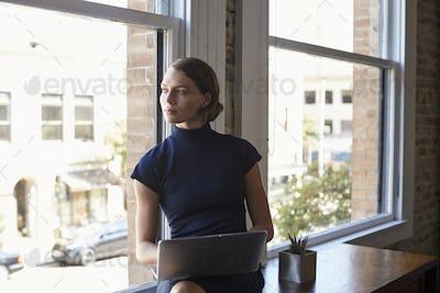 Businesswoman Sitting By Window Working On Laptop