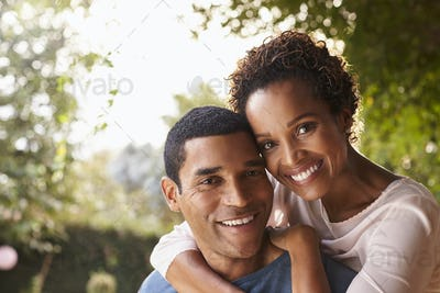 Young black couple piggyback in garden looking at camera