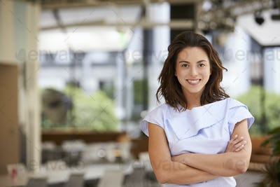 Portrait of young mixed race businesswoman with arms crossed