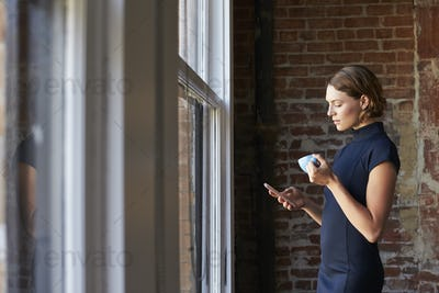 Businesswoman Checking Phone Standing By Office Window