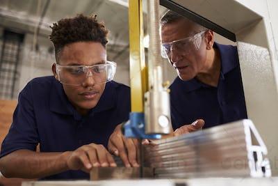 Carpenter Training Male Apprentice To Use Mechanized Saw