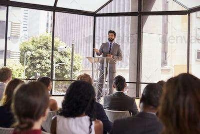 Hispanic man presenting business seminar to audience