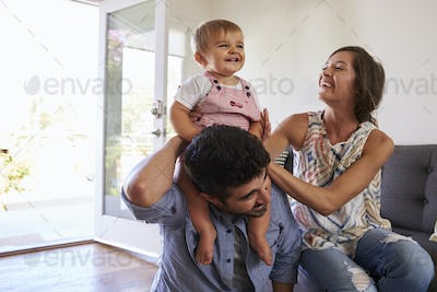 Parents Playing With Baby Daughter On Sofa At Home