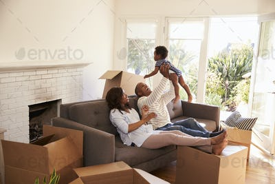 Parents Take A Break On Sofa With Son On Moving Day