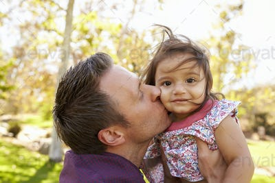 Father holding and kissing his young daughter in a park