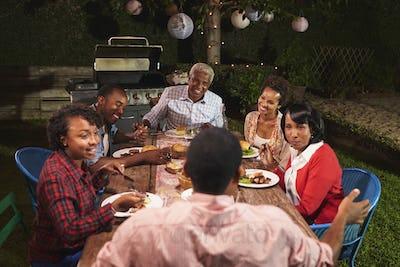 Adult black family talking at dinner in their garden