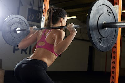 Rear View Of Woman In Gym Lifting Weights On Barbell