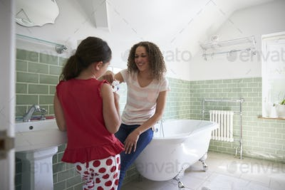Daughter Brushing Teeth In Bathroom With Mother