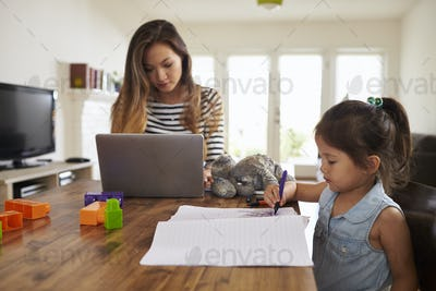Mother Works On Laptop As Daughter Draws Picture In Book