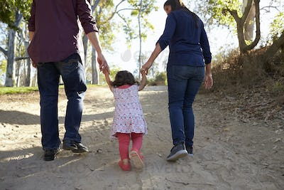 Parents and young daughter walk hand in hand on a rural path