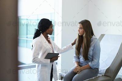 Doctor Talking To Unhappy Teenage Patient In Exam Room