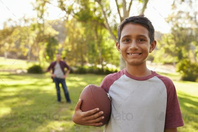 Portrait of boy holding football in park, dad in background