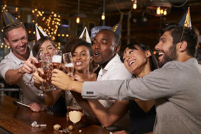 Friends toasting with champagne at New Year's party in a bar