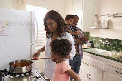 Family At Home Preparing Meal In Kitchen Together