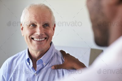 Doctor Meeting With Mature Male Patient In Exam Room