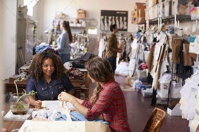 Two women talking at a table in a clothes design studio