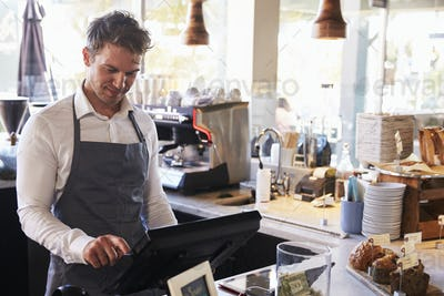 Male Employee Working At Delicatessen Checkout