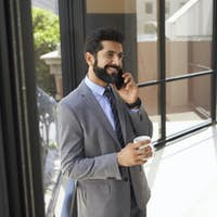 Middle aged Hispanic businessman using phone and holding cup