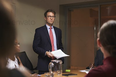 Young white businessman addresses team at meeting, low angle
