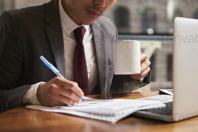 Businessman working on document holding coffee mug, close up