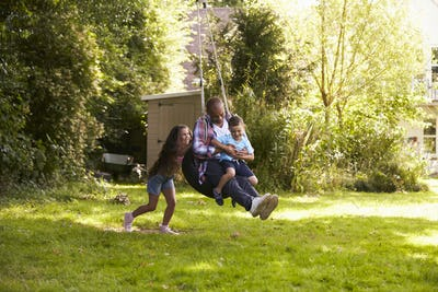 Daughter Pushing Father And Son On Tire Swing In Garden