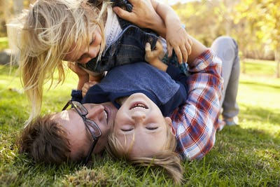 Two young kids lying on top of their dad in a park