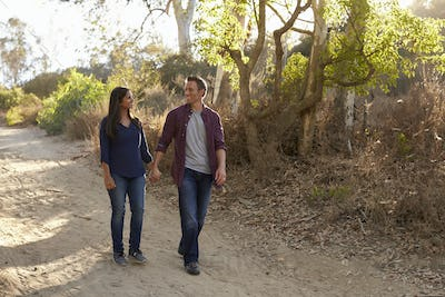 Mixed race couple walking in park holding hands, front view