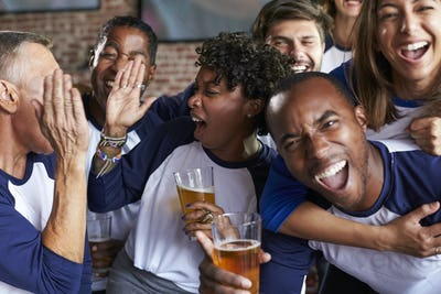 Portrait Of Friends Watching Game In Sports Bar On Screens