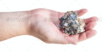 side view of zinc and lead ore on male palm