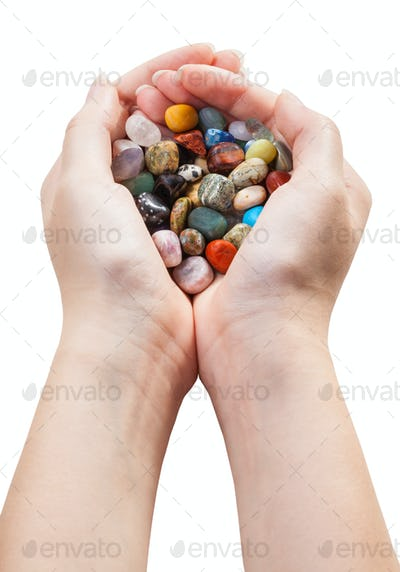 above view of handful with various gemstones
