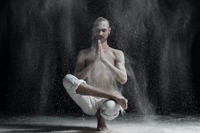 Young man doing yoga. Half Lotus Toe Balance