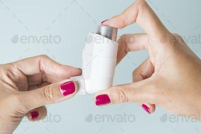 Hands hold an aerosol inhaler
