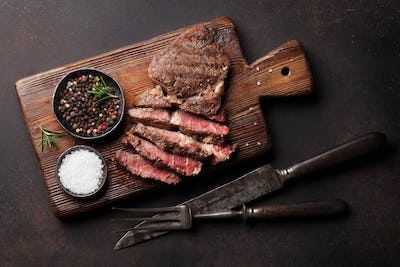 Grilled beef steak with spices on cutting board