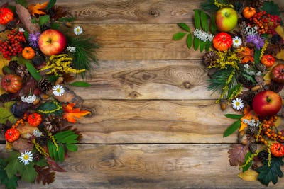 Thanksgiving decor with pumpkin, apples and green leaves on wood
