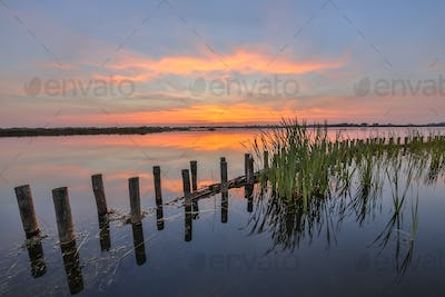 Sunset over lake with bank protection barrier