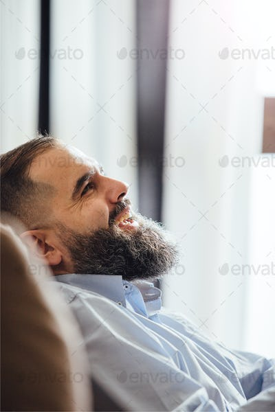 Side view of laughing bearded man