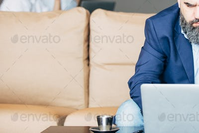 Half face of bearded businessman with laptop