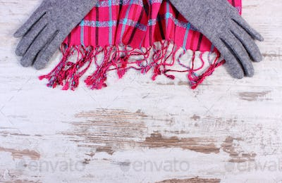 Womanly gloves and colorful shawl, copy space for text on old rustic board