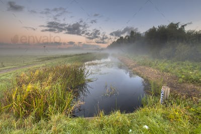 Sunrise over river with water level measuring rod