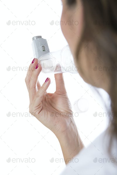 Young woman inhales a medicament from a space chamber