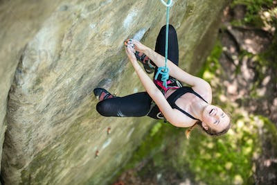 Young woman beginner climbing vertical cliff