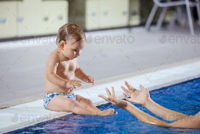 Young woman catching little son sitting poolside