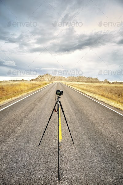 Professional photo equipment on an empty road at sunset.