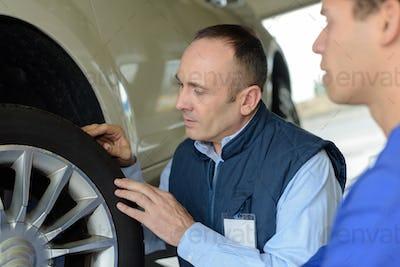 Mechanic checking vehicle tyre