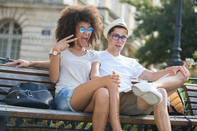 Young couple sat on bench, woman making funky gesture