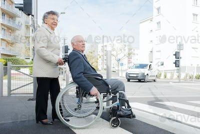 Elderly lady pushing husband in wheelchair across road