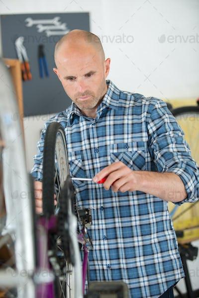 Mechanic working on bicycle wheel